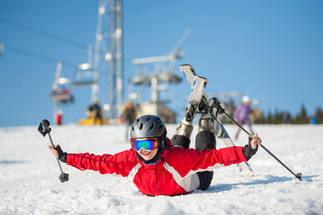Skier female in ski goggles lying with raised arms on snowy slope at mountain top in sunny day with ski lifts and blue sky in background. Close-up