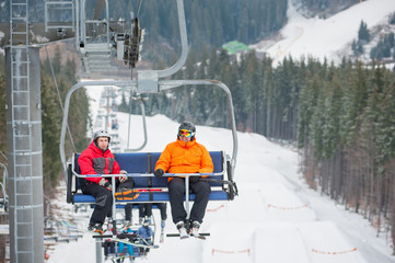 Skier and snowboarder riding up to the top of the mountain on ski lift, with beautiful view nature