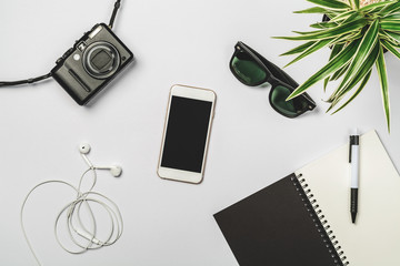 Flat lay photography with smart phone, earphone, notebook and pe