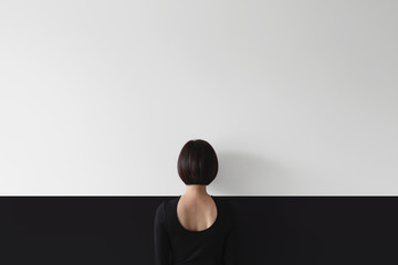 Rear view of woman standing facing wall