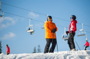 Happe couple man and woman wearing ski goggles standing with skis on mountain top at a winter resort in sunny day with ski lifts and blue sky in background.