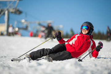 Woman wearing ski goggles, helmet, red jacket, gloves and pants lying with skis on snowy at mountain top and looking away in sunny day with ski lifts and blue sky in background. Bukovel, Ukraine
