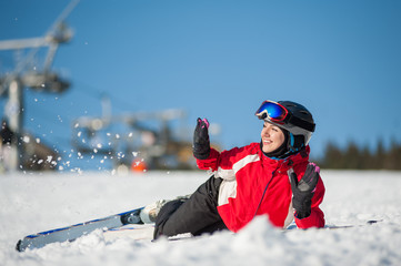 Smiling woman skier lying with skis on snowy at mountain top and throws snow in sunny day, having fun at a winter resort, ski lifts and blue sky in background. Close-up