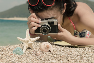 Young woman taking a photo of sea shells with retro camera at the beach. Summer accessories and summer vacation concept.