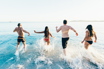 Rear view of a group of young multiethnic friends women and men running on the beach to the sea in summertime - happiness, summer, friendship concept