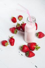Strawberry yogurt with fresh strawberries on a white wooden background