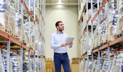happy businessman with tablet pc at warehouse