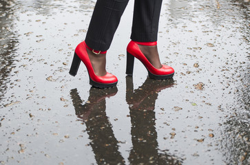 Red shoes high-heeled on wet asphalt.