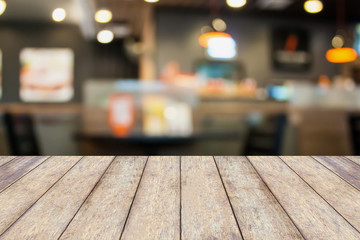 Empty wood table with cafe restaurant blur background with bokeh