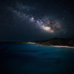 Milky way over the coast with a blue sea