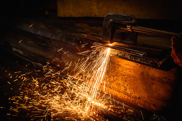 Worker cutting steel with acetylene welding cutting torch.