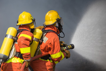2 firefighters spraying water in fire fighting with dark smoke b