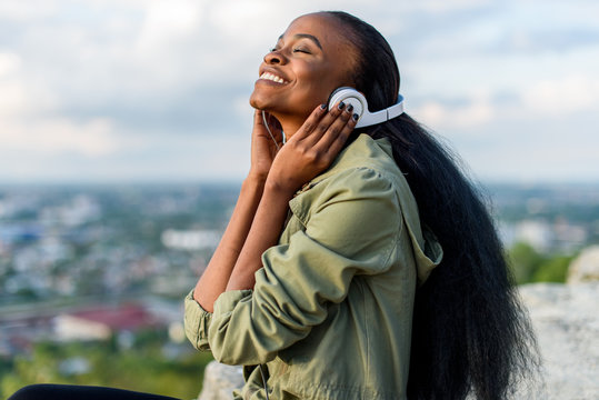 Close-up portrait of happy smiling young black african american woman listening to music. Blurred cityscape on background