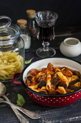 Italian pasta with eggplant and tomato sauce and a glass of red wine. On a dark wooden background. Healthy vegetarian food