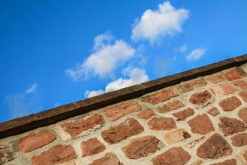 Unüberwindliche Mauerkante vor blauem Himmel