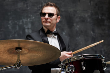 Blurred handsome man in sunglasses and suit playing a drum
