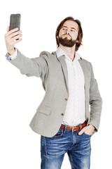 bearded young business man taking selfie smiling. portrait isola