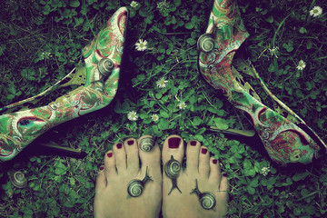 Woman's bare feet next to high heeled shoes, snails on feet