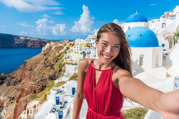Wall Mural - Europe travel selfie Asian woman in Oia village, Santorini. Cute happy smiling tourist girl taking self-portrait picture with smartphone during summer vacation in famous European destination, Greece.