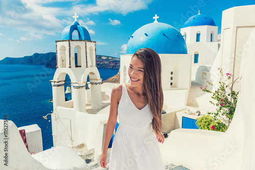 Wall mural Santorini travel tourist woman on vacation in European destination walking on stairs. Asian girl in white dress visiting three blue domes in Oia village, greek island. Summer Europe holidays.