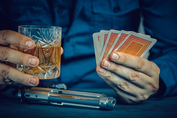 gangster with gun holding whiskey glass and playing poker
