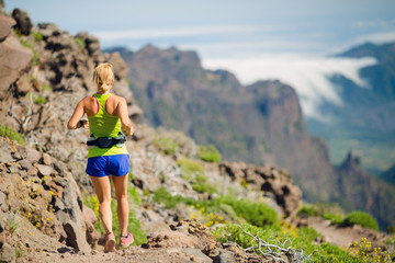 Young woman running in mountains on summer day