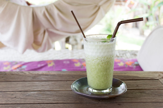 Fresh organic green tea drink with ice cubes served in a glass with a brown drinking straw and a handmade plate underneath. Hammock and natural surroundings in the background.