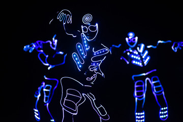Wall Murals Music Band dancers in led suits on dark background, colored show