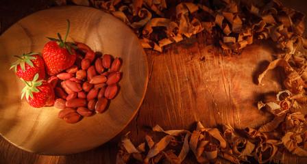 Клубника из арахисом на деревянной тарелке из акации, в рамке из стружки