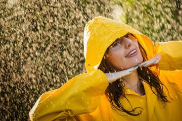 Portrait of happy woman wearing yellow raincoat enjoying the rain. showing two fingers.