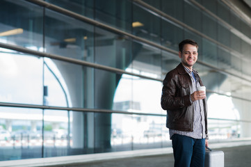Young handsome man with coffee cup and suitcase in the airport