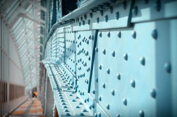 In de dag Brug Metal poles pedestrian covered bridge with lots of rivets. Vintage tinted.