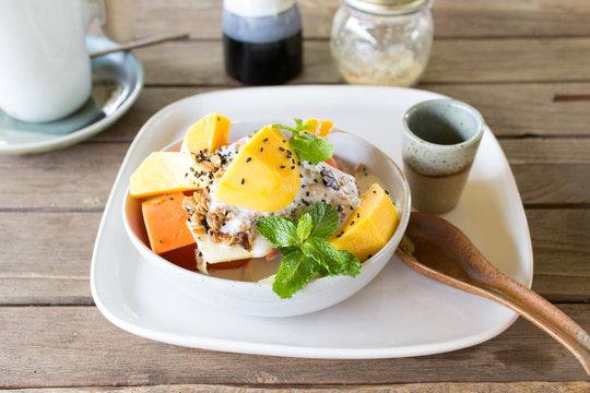 Mango, papaya, melon and pineapple fruit salad served with yogurt, milk, honey, sesame seeds and muesli. Porcelain bowl, plate and spoon are handmade.
