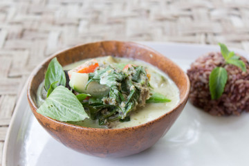 Homemade Green Thai Curry served with brown rice in a bowl and a plate. Originally made in Thailand.