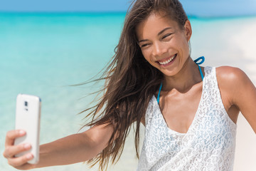 Cheerful young woman taking fun mobile phone selfie photos of herself on beach holidays during summer tropical travel vacation. Happy healthy Asian mixed race beauty girl smiling at smartphone.