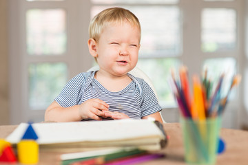 Blond boy laughing and crayons in front of him