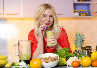 Beautiful young blonde drinking smoothie in her kitchen