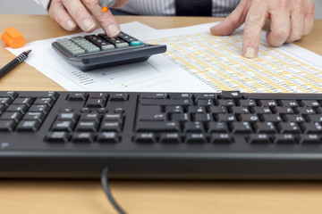 Financial account busy calculating at his desk