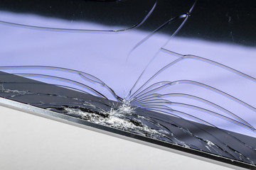 Broken iPad with a shattered glass screen on white background