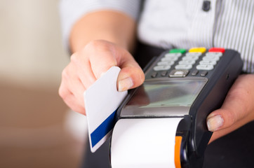 Women hand swaping a white credit card on a payment machine. Paper