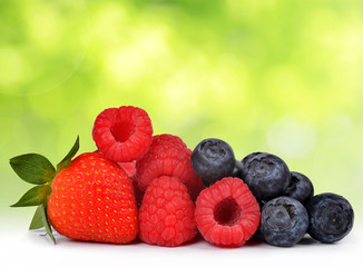 Strawberry with blueberries and raspberries on green natural background.