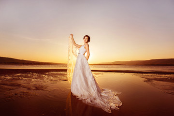 Beautiful bride in long wedding dress is holding veil at sea sunrise