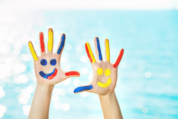 Closeup image of hands with colorful paint at blue summer sky