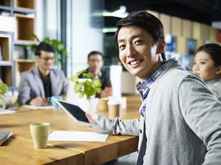 young asian businessman looking at camera