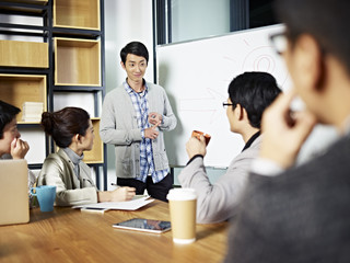 young asian businessman facilitating a workshop discussion