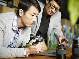 two asian photographers working in studio