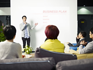 young asian man presenting business plan in front of investors