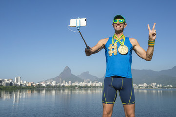Athlete taking selfie wearing gold medals with bright yellow emoji faces with smartphone on selfie stick in Rio de Janeiro, Brazil