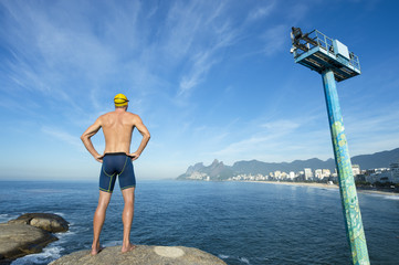 Athlete swimmer with swimming cap standing with hands on hips in front of the Rio de Janeiro skyline at Arpoador, Ipanema Beach