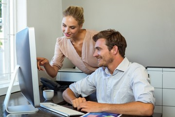 Female colleague pointing on computer at office